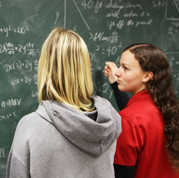 Two female students calculating math problems